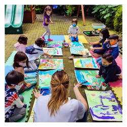 Photo shows a group of children sitting on the ground with large, colourful paintings in front of th