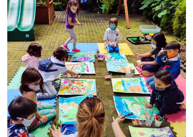 Photo shows a group of children working on large paintings. They are sitting on the floor with the teacher who is talking to them.