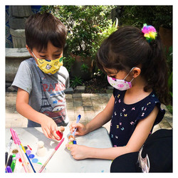 Photo shows two students wearing masks painting wooden dolls outside.