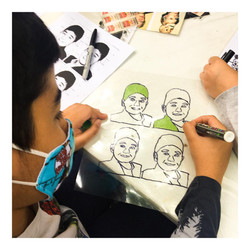 Photo shows a student wearing a mask faicng away from the camera. He is drawing.