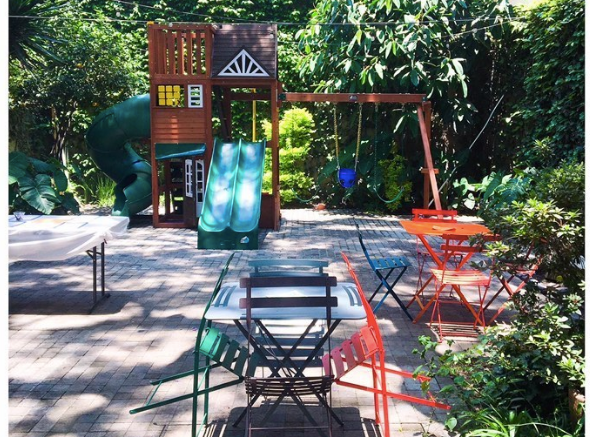 Photo shows the location of this class from a side angle. In the foreground are individual metal tables with chairs and in the background is the play area.