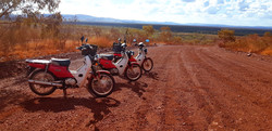 Postie bikes tour on a red dirt road