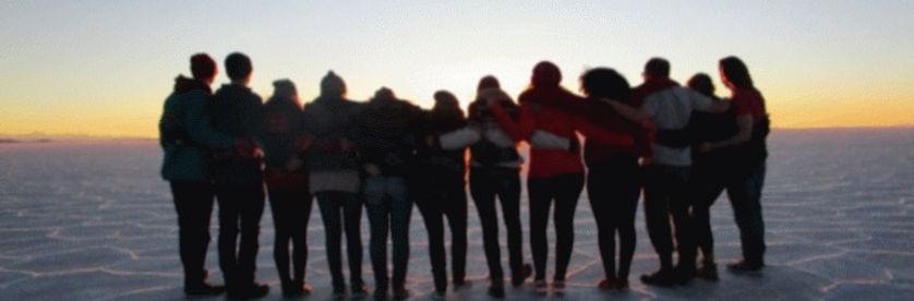 Gruppe von zwölf jugendlichen Freiwilligen in der Salzwüste Salar de Uyuni