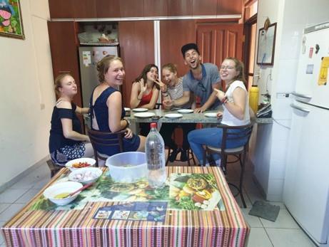 Gruppe von Freiwilligen in Bolivien, die zusammen während der Weihnachtszeit an einem Tisch sitzen.