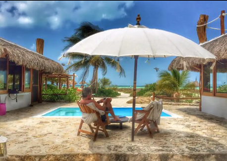 pic of the back of a man sitting outside under an umbrella, looking at the water