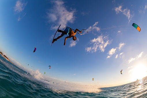 low-angle-shot-person-surfing-flying-parachute-same-time-kitesurfing.jpg