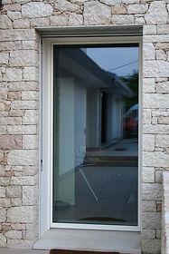 Serramento in legno/alluminio con effetto di complanarità tra telaio e anta nella parte esterna del serramento.