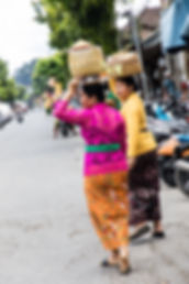 Femme en habit pour se rendre au temple avec des boites à offrande