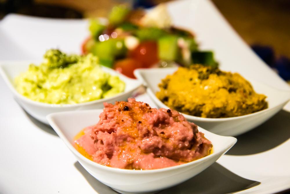 Pink humus on a set of mezze