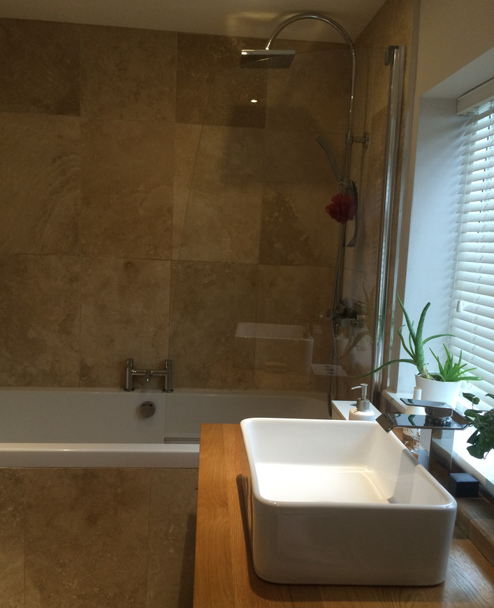 Refurbed bathroom with travertine tiles and oak unit