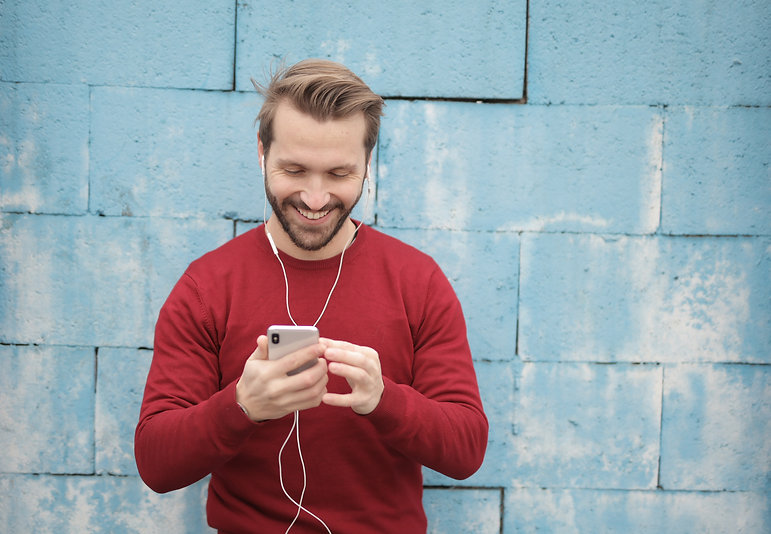 cheerful-young-man-listening-to-music-in