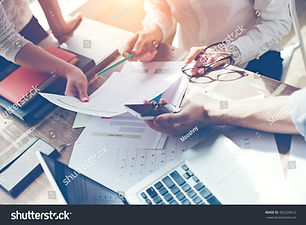 stock-photo-business-team-brainstorming-marketing-plan-researching-paperwork-on-the-table-