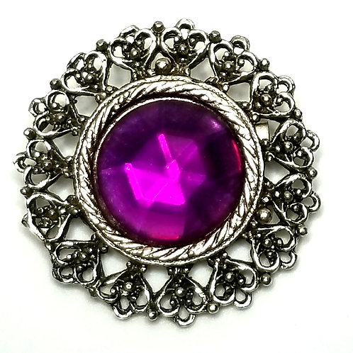 Designer by provenance, brooch, ornate motif, purple faceted stone, silver tone.