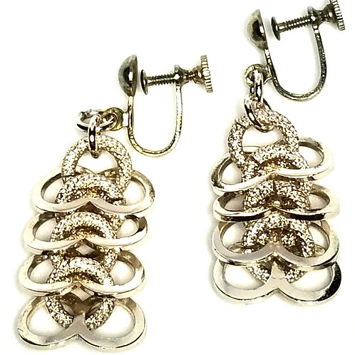 Designer by provenance, earrings, screw back dangles, loops motif, silver tone.