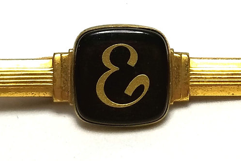 Designer by Hickok USA, tie clip, initial E motif, black in gold tone.