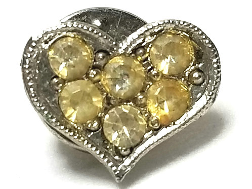 Designer by provenance, pin, heart motif, yellow stones, silver tone.