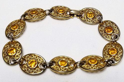Designer by Emmons, bracelet, yellow rhinestones in gold tone pot metal.
