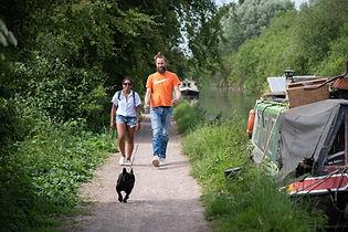 Couple walking dog along towpath