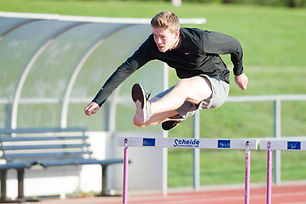Male adult jumping over a hurdle on an outdoor track