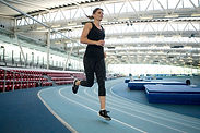Woman running on a blue indoor running track