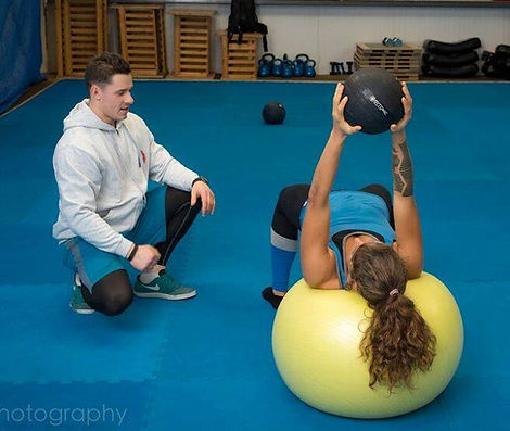 Personal Trainer Finn Glenn helps a client build muscle and get lean on swiss ball with medicine ball in kenmare's dojo.