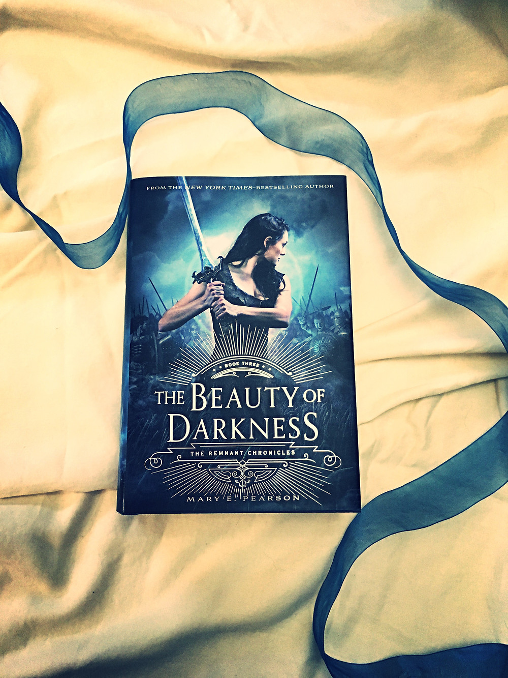Photo of: The Beauty of Darkness book on a cream background, with a blue ribbon arranged around the book.