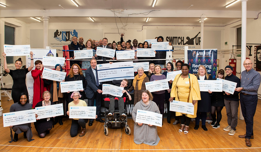 Community group picture - all holding their funding cheques in front of a boxing ring