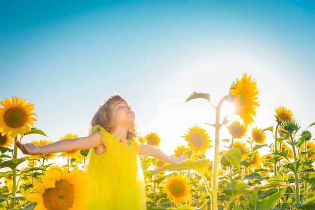 Happy child having fun in spring field a