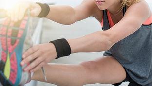 woman stretching wearing sweatband