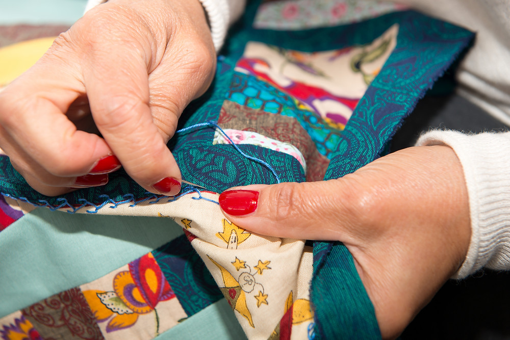 Hands sewing on a patch to a quilt