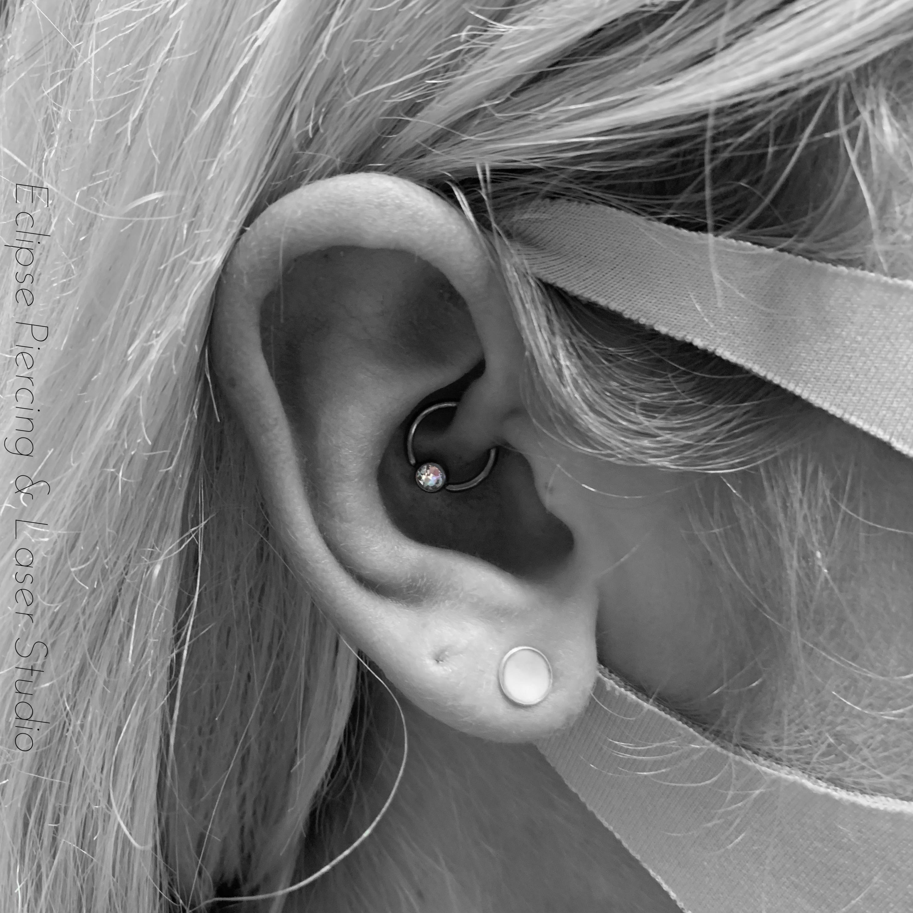 Daith piercing with a ball closure ring and ab crystal gem