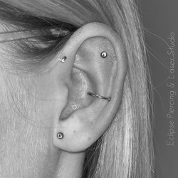 Orbital piercing with a segment ring and flat and anti-lobe piercings with crystal gems
