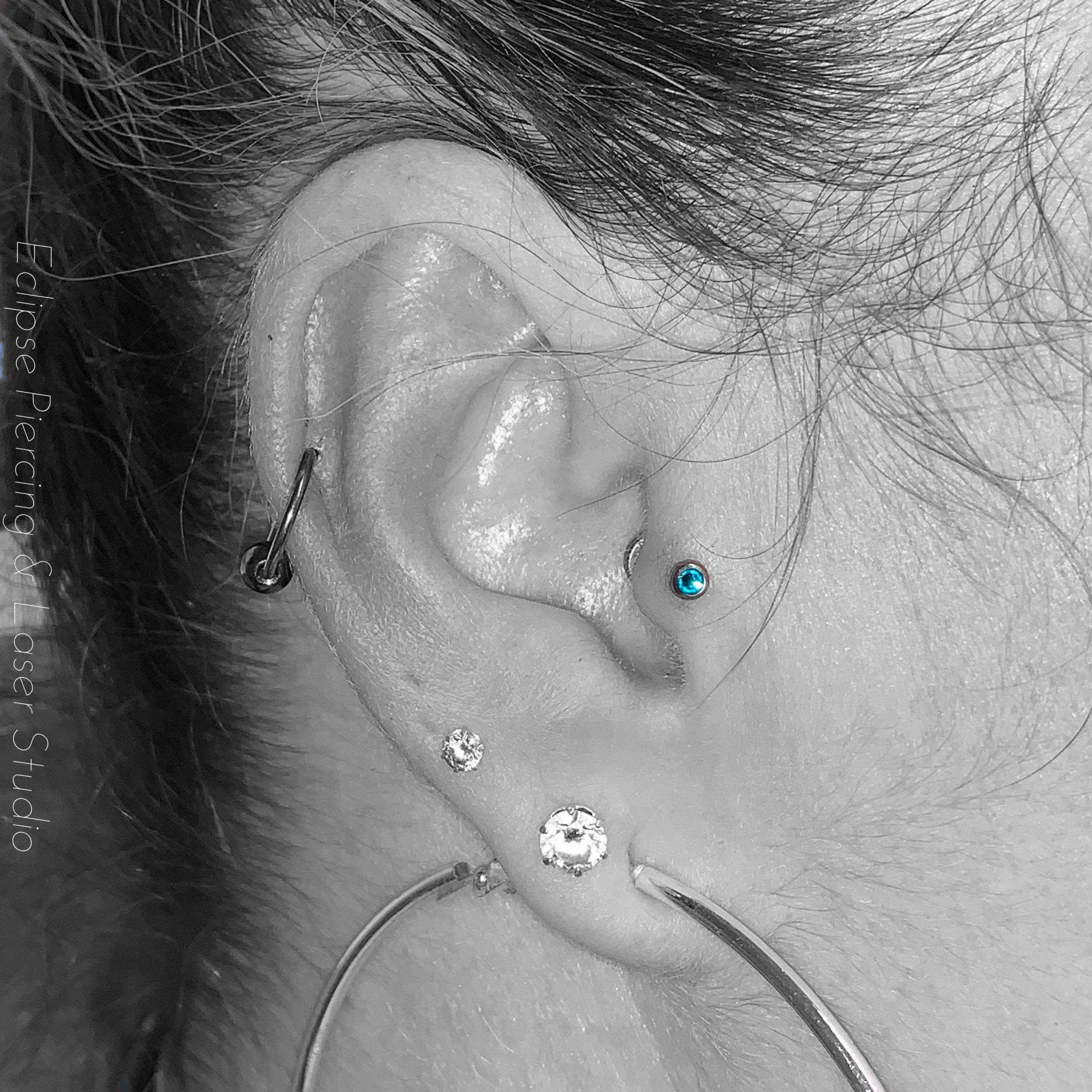 Helix piercing with a ball closure ring and a tragus piercing with a blue zircon crystal gem