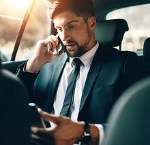 man met tablet en telefoon op achterbank