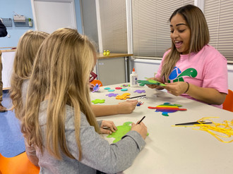 Staff helps children learn and play with turtle crafts.