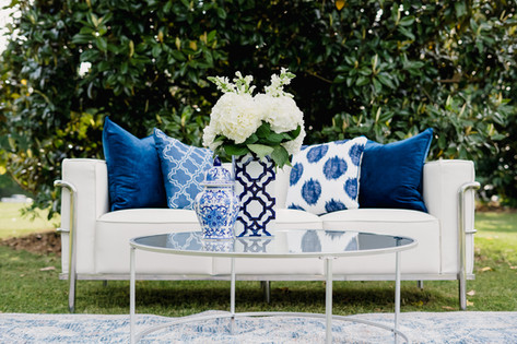 White lounge sofa, blue and white pillows and decor