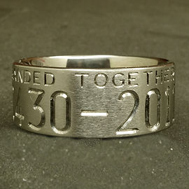 Titanium duck ring showing part of an engraved wedding date and the word together