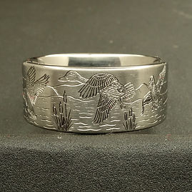 Hand engraved wedding band with flying ducks