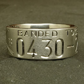 Titanium duck ring showing part of an engraved wedding date and the word banded