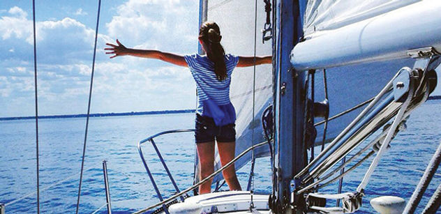 Young girl on bow of sailboat