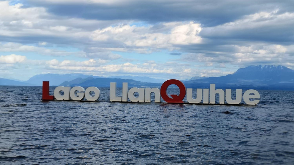 Sign Lago Llanquihue in lake with mountains in background