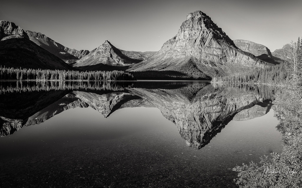Sinopah Mtn across Two Medicine Lake in Glacier National Park. This year was my sixth year going to Glacier in August, and Two Medicine is always one of the stops in hopes of getting a brilliant sunrise. This is not a picture of a brilliant sunrise but rather was better seen in black/white. Most of the time it is very windy, but on this day, the water was calm allowing for a nice reflection.