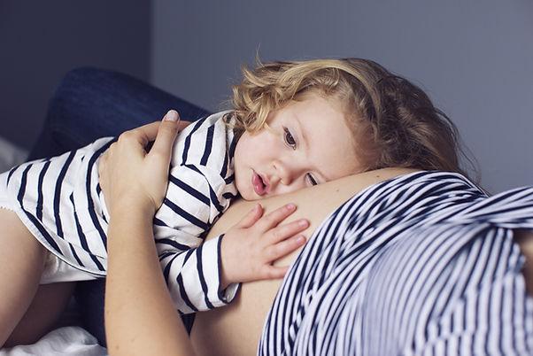 Jeune fille couchée sur le ventre de sa maman enceinte