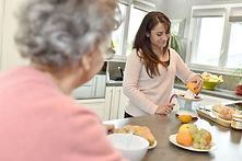Home helper serving breakfast to elderly