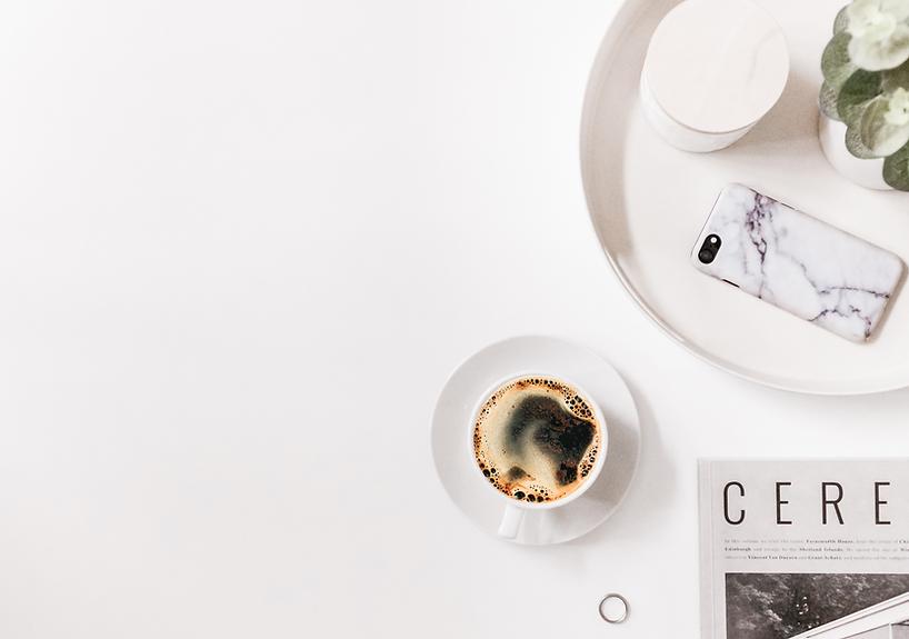 tasse de café posée sur une table avec une bougie, un téléphone portable et un magazine