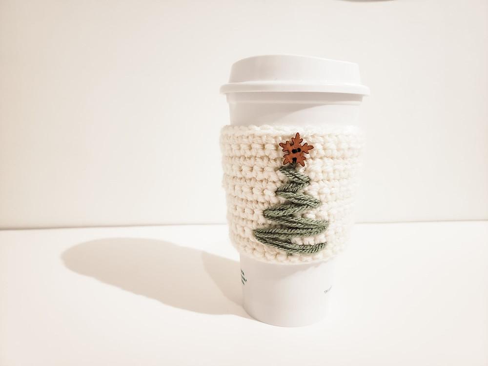 The crochet christmas tree cozy displayed on a Starbucks mug.
