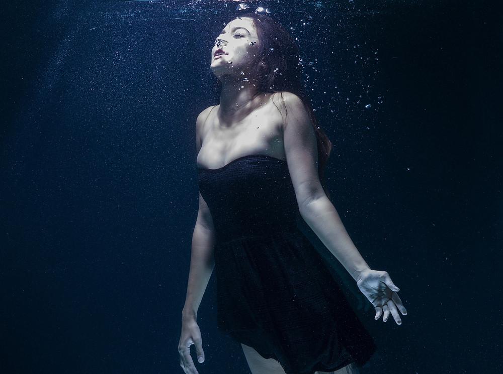 Mulher com vestido preto debaixo de água