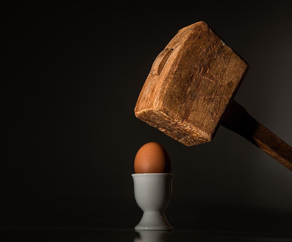 Ovo numa taça com antigo martelo de madeira grande