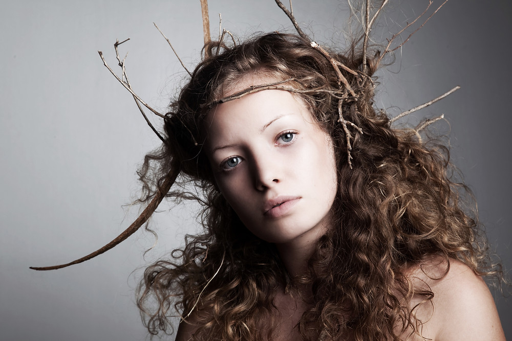 Beautiful woman with twigs in her long, wavy hair