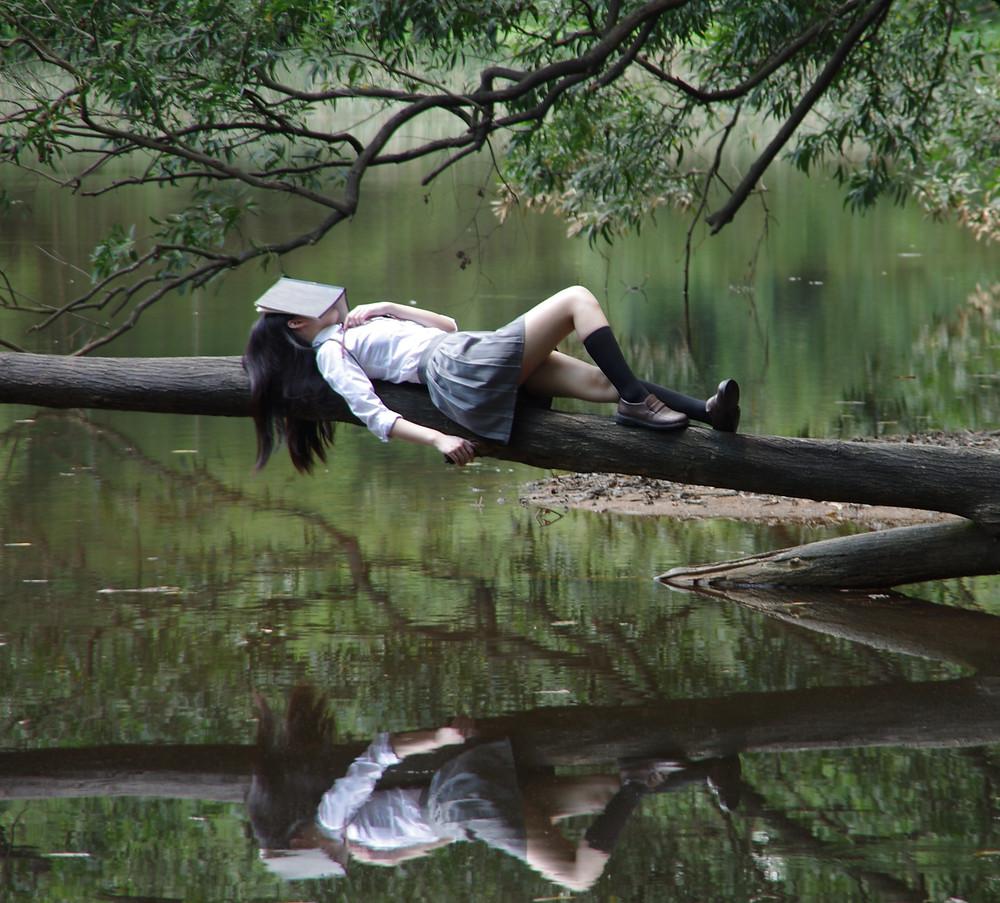 Rapariga deitada sobre um tronco de árvore com livro a tapar rosto